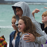 A hooded Quade Cooper poses for photographs with youngsters during the Australian teams recovery session at  Takapuna Beach at the IRB Rugby World Cup tournament, Auckland, New Zealand, 17th October 2011. Photo Tim Clayton...