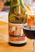 A half empty full bottle from Domaine Pierre Usseglio and a glass of wine, Chateauneuf-du-Pape, Vaucluse, Rhone, Provence, France