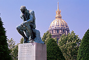 Le Penseur bronze statue by August Rodin in the gardens at the Rodin Museum, Paris France. The dome of the Invalides is in the background