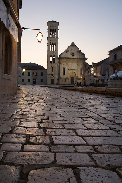 Europe, Croatia, Dalmatia, Hvar Island, Hvar town, main square, known as Trg svetog Stjepana, with cobblestones and St. Stephen's Cathedral, built 16th century, at dusk.