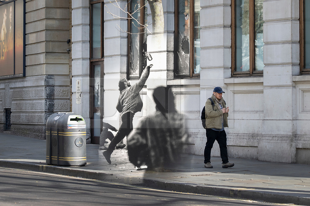 © Licensed to London News Pictures. 25/03/2020. London, UK. In this combined image a protester throws a brick at the windows of a bank on Charing Cross Road  during the London poll tax riots on March 31st 1990 overlaid on the same location today. The protest on the last day of March in 1990 started peacefully when thousands gathered in a south London park to demonstrate against Margaret Thatcher's Government's introduction of the Community Charge - commonly known as the poll tax. Marchers walked to Whitehall and Trafalgar Square where violence broke out with the trouble spreading up through Charring Cross Road and on to the West End. Police estimated that 200,000 people had joined the protest and 339 were arrested. The hated tax was eventually replaced by the Council Tax under John Major's government in 1992.  Photo credit: Peter Macdiarmid/LNP
