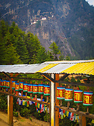 Row of prayer wheels on the trail leading to the Taktsang Monastery with the monastery on the hillside in the distance