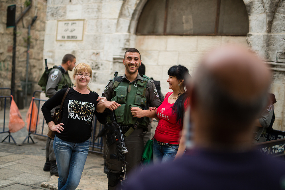 An Israeli Border Police Man poses for a photograph with tourists at HaGai Street, or al Wad Street in the Muslim quarter of the Old City of Jerusalem, Israel, on April 10, 2016.