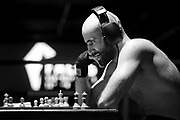 """Amateur Chessboxer Mohamad Khadijah is contemplating his next move in a round of chess during a chessboxing match at the Intellectual Fight Club in Berlin, Germany on the 15th of December 2017. <br /> Chessboxing is a literal combination of chess and boxing in a single match, demanding the players to quickly shift between mental and physical skills. The battle consists of 11 alternating rounds of chess and boxing, each lasting for 3 minutes. A game is won by checkmate, knockout or the judge's decision. <br /> The sport first got conceived of by the Slovak Bosnian comic book creator Enki Bilal, who introduced it in his futuristic graphic novel """"Cold Equator"""". Inspired by the book Dutch artist Iepe Rubingh staged the first fight in Amsterdam in 2003, which he himself fought and won. After that Iepe moved to Berlin and proceeded to found chessboxing-global.com, an organisation that strives to make the new sport popular worldwide."""