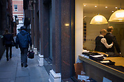 A gentleman client has a fitting for a new made-to-measure suit, seen through a City taylor's window. Feeling under the arm of his client, the taylor makes sure his measurements are correct before making final adjustments for the final garment. Hanging in the shop are other suits and jackets, awaiting buyers. But outside are two people unaware as they pass the shop window, walking through a narrow medieval lane, a backstreet in the City of London, the capital's financial heart, founded by the Romans in 43AD.