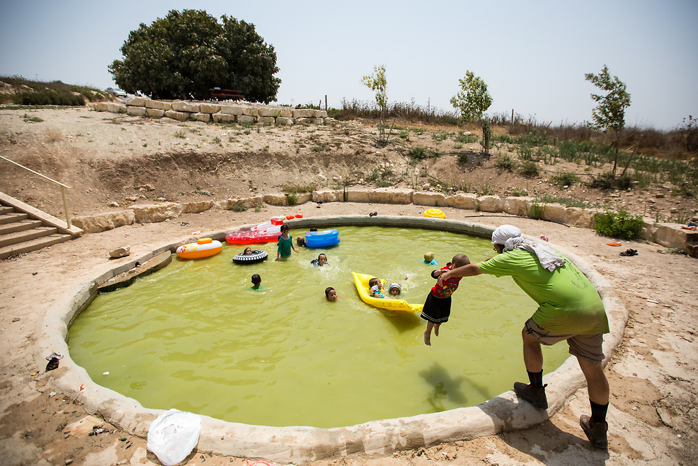 Jewish Israeli children enjoy the cold water of a spring pool, during a hot summer day in the West Bank Jewish settlement of Yitzhar, south of the Palestinian West Bank city of Nablus, on August 5, 2015.