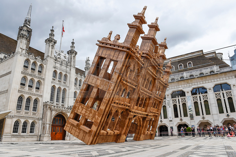 © Licensed to London News Pictures. 21/07/2019. LONDON, UK.  The People's Tower, is pulled over in Guildhall Yard in the City of London. The monumental cardboard structure, built by artist Olivier Grossetête aided by a local volunteers comprises over 1,000 boxes and stands 20 meters high - it is inspired by the Guildhall building.  The four day construction process culminates in the structure being ceremonially toppled and torn down.  Photo credit: Stephen Chung/LNP