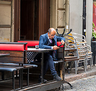 Stockholm, Sweden -- July 16, 2019. A Swedish businessman has coffee and reads his phone at a cafe in Old Town, Stockholm.