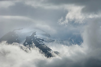 Peaks of the Chugach Range Alaska appearing through storm clouds