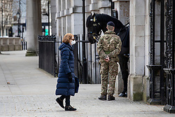 © Licensed to London News Pictures. 20/03/2020. London, UK. A woman wearing a face mask walks past a soldier in Westminster as the Coronovirus outbreak continues to escalate in the capital. Photo credit: Rob Pinney/LNP