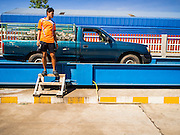 """15 DECEMBER 2014 - CHUM SAENG, RAYONG, THAILAND: A farmer stands in front of his pickup truck while his load of latex is weighed at a rubber buying station in Chum Saeng, Thailand. Thailand is the second leading rubber exporter in the world. In the last two years, the price paid to rubber farmers has plunged from approximately 190 Baht per kilo (about $6.10 US) to 45 Baht per kilo (about $1.20 US). It costs about 65 Baht per kilo to produce rubber ($2.05 US). Prices have plunged 5 percent since September, when rubber was about 52Baht per kilo. Some rubber farmers have taken jobs in the construction trade or in Bangkok to provide for their families during the slump. The Thai government recently announced a """"Rubber Fund"""" to assist small farm owners but said prices won't rebound until production is cut and world demand for rubber picks up.    PHOTO BY JACK KURTZ"""