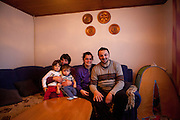 Former refugee Elvis Causevic with his wife Irma and his mother Dzevada (left) holding their daughter Adna (left, 3 1/2) and son Aldin (1 1/2) in the living room at the  families house in Hadžići. The family settled here after the war ended in Bosnia. Hadžići is a town and a municipality located about 20 km south west of Sarajevo city but within the Sarajevo Canton of Bosnia and Herzegovina. According to the census of 2013, Hadžići municipality has a population of 23,891 residents.