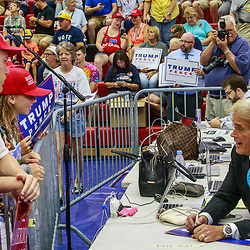 Mechanicsburg, PA – August 1, 2016: A Trump supporter asks John Roberts, Fox News Correspondent, for an autograph on a campaign sign at the Donald Trump political rally.