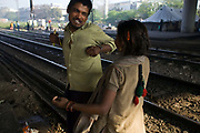 Patti-Das plays and flirts with a young girl on a piece of waste ground beneath a flyover near Okhla station. New Delhi, India. New Delhi, India