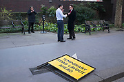 Three people smoking on the street in front of a sign which reads Temporary Road Layout Ahead. Two men a lighting up while the woman smokes while texting. London, UK.