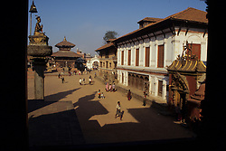 Asia, Nepal, Kathmandu Valley, Bhaktapur. Sun Dhoka (Golden Gate) & Royal Palace in Durbar Square viewed through temple window.