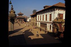 Asia, Nepal, Kathmandu Valley, Bhaktapur. Sun Dhoka (Golden Gate) & Royal Palace in Durbar Square viewed through temple window.
