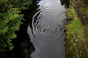 Wild bather swims breast stroke in mountain waters of River Shiel in Moidart on the Ardnamurchan peninsular, Western Scotland.