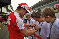 O piloto espanhol Fernando Alonso autografa camisetas de escolares que visitam os boxes do Grande Prêmio de F1 do Brasil no Autódromo de Interlagos em 07 novembro de 2010, em São Paulo, Brasil. FOTO: Jefferson Bernardes/Preview.com