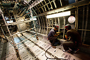 Employees work on the fuselage of a G.222 aircraft  at the Alenia Aeronautica plant at Capodichino, in Naples, Italy, on Monday, Sept. 6, 2010.