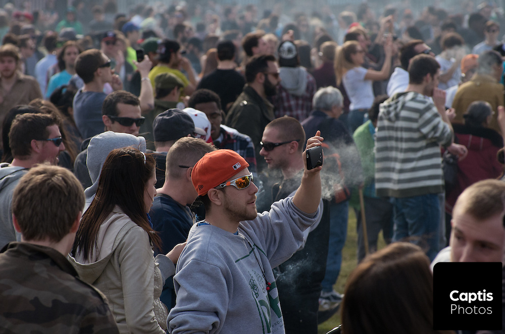 A man captures a video on his phone while smoke rises from the crowd who lit up marijuana at 4:20pm to mark 4/20. April 20, 2014.