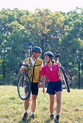 Couple walking together with bicycles on their shoulders