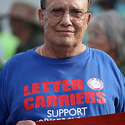 A U.S. Postal worker pickets during a parade prior to the start of the Republican National Convention in Tampa, Fla. on Wednesday, August 29, 2012. (AP Photo/Alex Menendez)