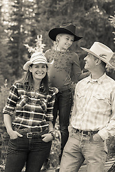family of three outdoors in cowboy hats
