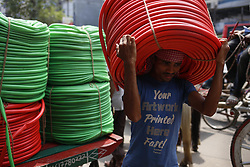 April 26, 2018 - Dhaka, Bangladesh - A van driver delivers plastic tube on his head to a warehouse near a wholesale market in Dhaka. (Credit Image: © Md. Mehedi Hasan via ZUMA Wire)