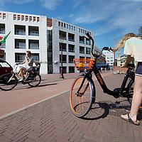 Nederland, Amsterdam, 9 juli 2017.<br /> De Amsterdamse start-up FlickBike test deze zomer een naar eigen zeggen 'vernieuwend deelfietsconcept'. Het experiment omvat duizend fietsen, die realtime te vinden zijn via een gratis app. Gebruikers downloaden de app, zoeken een fiets in de buurt en openen het fietsslot met hun telefoon.<br /> <br /> Anders dan bij veel bestaande deelfietsconcepten, laten fietsers een FlickBike gewoon achter op hun bestemming. Teruggaan naar een huurstalling of fietsverhuurstation is niet meer nodig.<br /> Op de foto: Meisje verstelt haar zadel vd Flick bike<br /> <br /> <br /> Foto: Jean-Pierre Jans