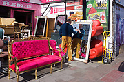 Shop owner writes a reduced price on an upright mirror with bright furniture on sale in a London street.A shop owner writes a reduced price on an upright mirror with bright furniture on sale in a London street. Writing on the glass with a marker pen the man has decided to tell us the original price of this item was #250 and he writes down a new, reduced value of #170, making us believe there are massive savings to be had on this home furnishing. Behind him is a garish pink sofa chair that was made in Egypt and imported to the UK capital where it and other pieces sit in bright sunshine, their colours looking tacky and cheap.