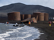 On Deception Island, rusting boilers and abandoned buildings date back to a shore-based whaling factory 1910-1931. In the South Shetland Islands near the Antarctic Peninsula, Deception Island has one of the safest harbors in Antarctica. Zodiac boats land cruise ship visitors on a black sand beach. Deception Island is the caldera of an active volcano, which caused serious damage to local scientific stations in 1967 and 1969. The island is now a tourist destination and scientific outpost, with research bases run by Argentina and Spain. The island is administered under the Antarctic Treaty System. The sea surrounding Deception Island is closed by ice from early April to early December.