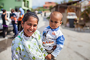 Roma girl holding a young boy and posing for a portrait at the Roma part of the city of Vinica in Macedonia during the European Immunization Week.