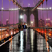 People walking across the Brooklyn Bridge.  The bridge is 1595.5 feet long and was completed in 1883.  It is a National Historic Landmark that connects Manhattan and Brooklyn by spanning the East River.