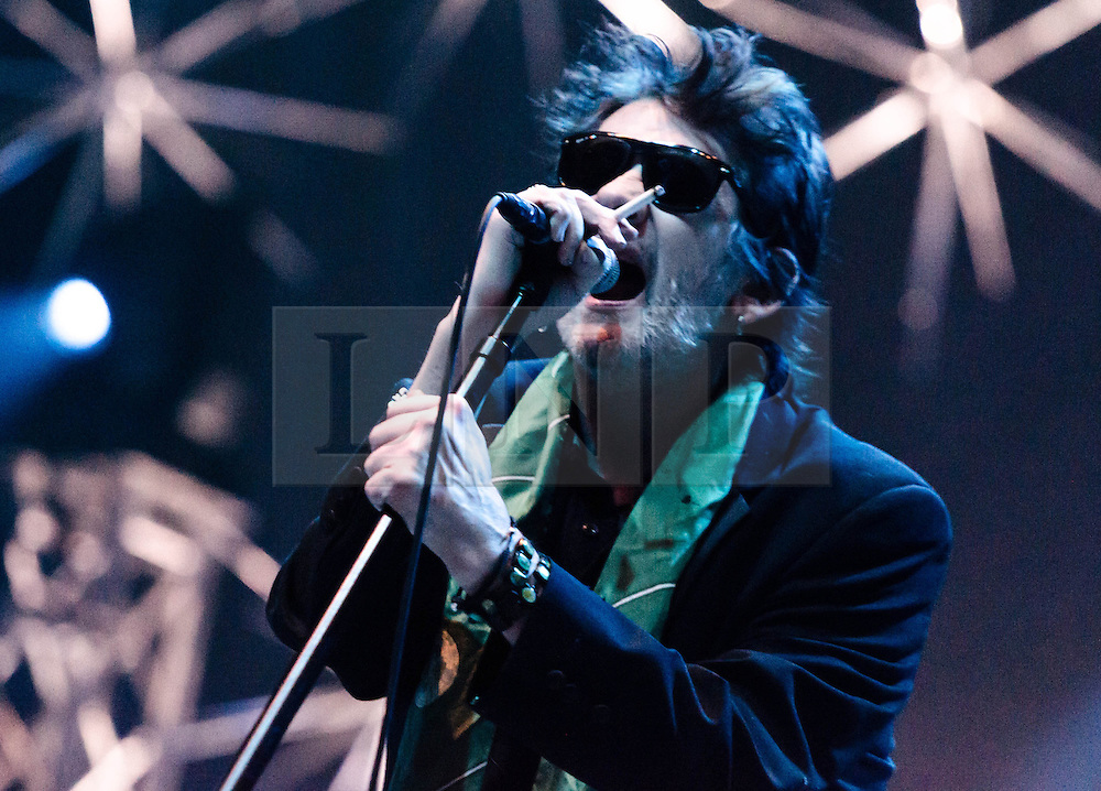© Licensed to London News Pictures. 20/12/2012. London, UK.   Shane MacGowan of The Pogues performing live with a cigarette at The O2 Arena for their only UK live date of 2012 as part of their 30th Anniversary Tour.  The Pogues are a Celtic punk band from London, formed in 1982 and fronted by Shane MacGowan.  Members include Shane MacGowan (vocals, guitar, banjo, bodhrán),.Spider Stacy (vocals, tin whistle), Jem Finer (banjo, mandola, saxophone, hurdy-gurdy, guitar, vocals), Andrew Ranken (drums, percussion, harmonica, vocals), .James Fearnley (accordion, mandolin, piano, guitar), .Philip Chevron (guitar, vocals),  Darryl Hunt (bass guitar),.Terry Woods (mandolin, cittern, concertina, guitar, vocals).     Photo credit : Richard Isaac/LNP