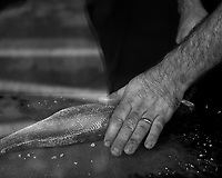 Cook Cleaning a Fish. Street Photography in Cascias. Image taken with a Fuji X-T3 camera and 35 mm f/1.4 lens.