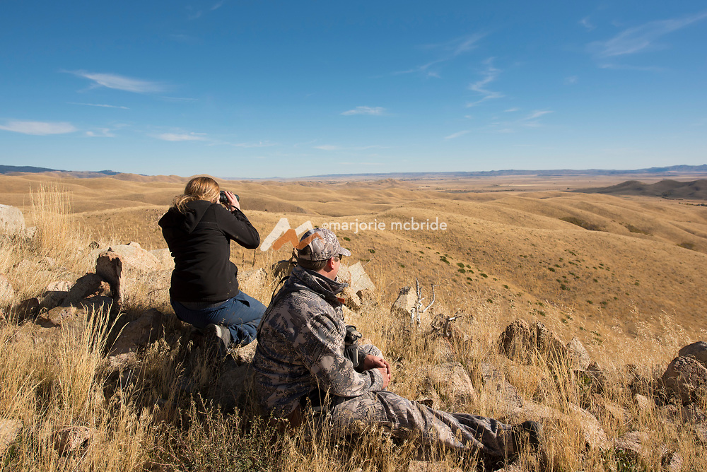 Father and daughter glassing from mountain top ledge while hunting together in Fairfield, Idaho. MR