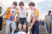 Jan Bos wordt in de VeloX2 geholpen door projectleider Paul Denissen (links) en Niels Lommers. Het Human Powered Team Delft en Amsterdam presenteert de VeloX2, de fiets waarmee ze het wereldrecord willen verbreken dat nu op 133 km/h staat. Jan Bos, een van de rijders die het record gaat proberen te verbreken, gaat de strijd aan met zijn broer Theo Bos op de gewone racefiets. Jan wint uiteindelijk glansrijk en haalt 77,2 km/h.<br /> <br /> With help of team captain Paul Denissen (left) and trainer Niels Lommers (right) Jan Bos gets in the VeloX2. Human Powered Team Delft and Amsterdam presents the VeloX2, the bike which they will attempt to set a new world record with. Jan Bos, on of the two cyclists who will try to ride faster than 133 km/h, is racing at the presentation against his brother Theo Bos, a former world champion and cyclist for the Rabobank Racing Team. Jan will defeat Theo, with a maximum speed of 77,2 km/h.