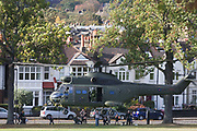 Locals are caught up in downdraught as ZA939, a Westland SA-330E Puma HC1 helicopter belonging to the RAF's 230 squadron, lifts off after a five minute touch down in Ruskin Park, south London. The RAF frequently make reconnaissance flights to this Lambeth open space for crew training purposes.