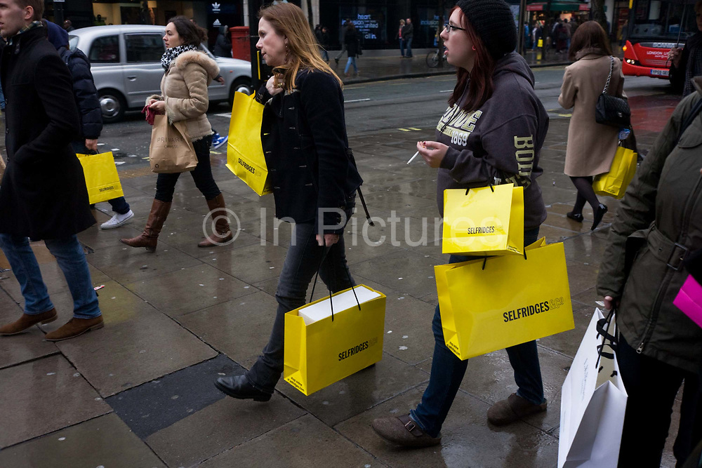 Women shoppers carry their purchases in yellow Selfridges bags as they leave the famous department store in London's Oxford Street. Amid crowds of fellow-shopaholics, the women walk down the pavement (sidewalk) laden with purchases. The economic recovers appears to have begun in earnest and retail therapy has attracted these Londoners to the West End, away from the larger, warmer shopping Malls on the outskirts of town. Selfridges was founded by Harry Gordon Selfridge. The flagship store in London's Oxford Street is the second largest shop in the UK (after Harrods) and was opened on 15 March 1909.