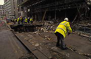 Two days after the Irish Republican Army IRA exploded a truck bomb on Bishopsgate, a main arterial road that travels north-south through Londons financial area, City of London engineering officials examine the huge crater left by the terrorist device, on 26th April 1993, in London, England.  Debris is strewn around the hole with drainage and road material. It was said that Roman remains could be viewed at the bottom of the pit the bomb created. One person was killed when the one ton fertiliser bomb detonated directly outside the medieval St Ethelburgas church. Buildings up to 500 metres away were damaged, with one and a half million square feet 140,000 m² of office space being affected and over 500 tonnes of glass broken. Costs of repairing the damage was estimated at £350 million. It was possibly the IRAs most successful military tactic since the start of the Troubles.