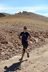 © Licensed to London News Pictures. 14/11/2013.<br /> <br /> British teenager Connor Brown, bib no. 5. <br /> <br /> Inaugural Volcano Marathon, Atacama Desert, Chile. The race took place in the Atacama Desert in Chile, beginning at an altitude of 4,400 metres (14,500 feet) in the vicinity of Lascar Volcano. It was a gruelling affair for many of the competitors who had to encounter some challenging hills and manage the impact of the heat and oxygen deprivation. The average altitude of the entire race was close to 4,000 metres and temperatures reached the mid 20s Celsius, or almost 80 Degrees Farenheit.<br /> <br /> Photo credit : Mike King/LNP<br /> <br /> Further information and link to video here: https://www.dropbox.com/s/0277bepxvo0t8il/Marathon%20copy.txt