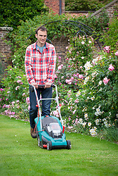 Mowing a lawn with an electric lawnmower.