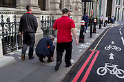 A businessman stops to tie a loose shoelace on Lombard Street in the City of London, aka The Square Mile the capitals financial district, on 3rd September 2019, in London, England.