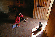 A guest relaxes in the winery guesthouse, a former 11th Century ermita (hermitage) at the Remelluri Winery.  Rioja, Spain. MODEL RELEASED.