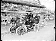 car with family posing next to the base of the Eiffel tower Paris around 1900