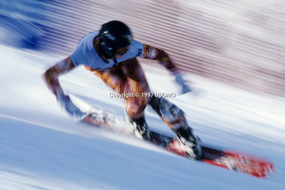 Blurred action of snowboarder racing downhill.