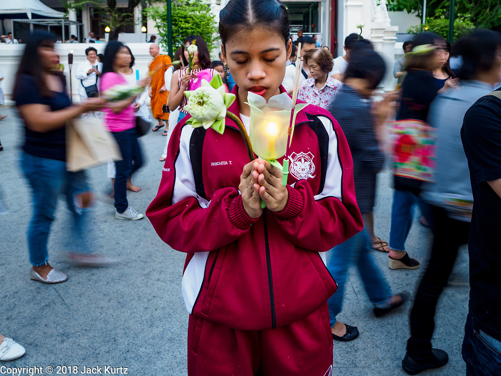 """01 MARCH 2018 - BANGKOK, THAILAND:    A nursing student from the Thai police hospital prays while people participate in a procession at Wat Pathum Wanaram in central Bangkok. Many people go to temples to perform merit-making activities on Makha Bucha Day, which marks four important events in Buddhism: 1,250 disciples came to see the Buddha without being summoned, all of them were Arhantas, or Enlightened Ones, and all were ordained by the Buddha himself. The Buddha gave those Arhantas the principles of Buddhism. In Thailand, this teaching has been dubbed the """"Heart of Buddhism.""""    PHOTO BY JACK KURTZ"""