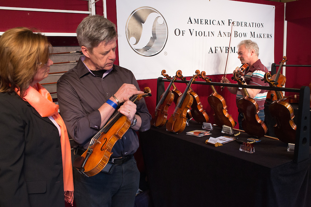 A couple examines the scroll of a violin in the booth of the American Federation of Viollin and Bow Makers.