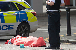©Licensed to London News Pictures 21/08/2020             Plumstead, UK. A police officer stands with the body. Parts of Plumstead high street in South East London are closed this morning after a man was fatally stabbed to death. It is believed the man was stabbed on Heron Hill a short distance away then transferred to Plumstead for the air ambulance. Photo credit: Grant Falvey/LNP